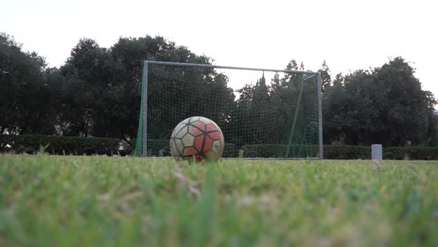 This footage features a long shot of a young male football player kicking the ball into the net in slow motion.For sport news, documentaries, vlogs, social media posts and videos related to football | Shutterstock HD Video #1012679534