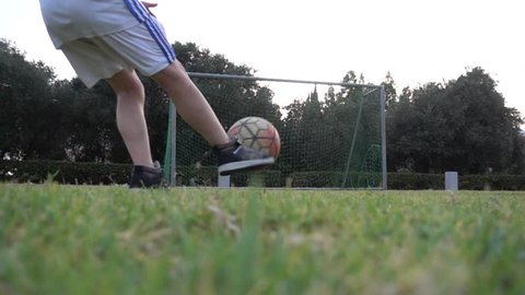 This footage features a long shot of a young male football player kicking the ball into the net in slow motion.For sport news, documentaries, vlogs, social media posts and videos related to football