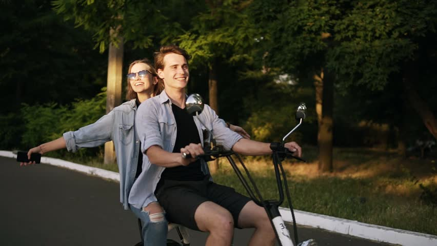 Happy, smiling couple riding electro bike in the park. Girl with outstretched hands. Enjoyment, hanging outdoors in the park, dating