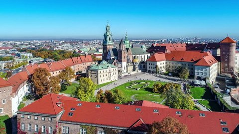 Royal Wawel Gothic Cathedral in Cracow, Poland, with Renaissance Sigismund Chapel with golden dome, Wawel Castle, yard, park and tourists. Aerial 4K approach video in the morning