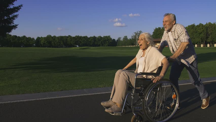 Side view of funny and cheerful happy senior couple enjoying outdoors. Senior bearded husband running and pushing wife in wheelchair. Happy woman raising arms and having fun. Steadicam shot | Shutterstock HD Video #1012737464