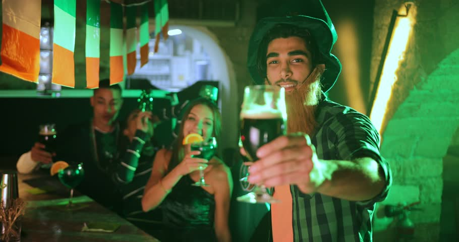 Young happy multi-ethnic friends drinking beer and cocktails at Saint Patrick's day pub celebrations