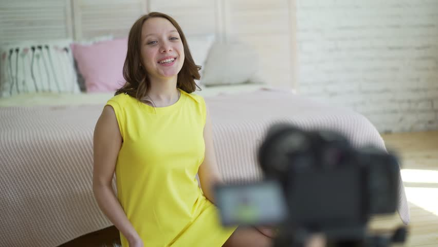Woman in yellow dress talking in front of camera to make a video blog. 72840fc10e6c