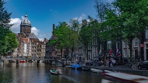 Amsterdam, Netherlands - June 1, 2018. Hyperlapse Timelapse in Amsterdam City Center with Church Architecture and Water Canal.