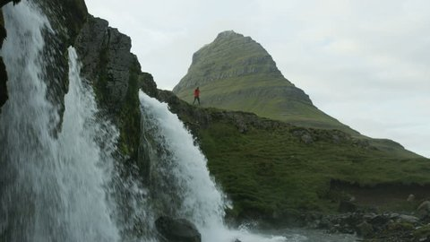 Woman walking down trail near Kirkjufell waterfall in Iceland