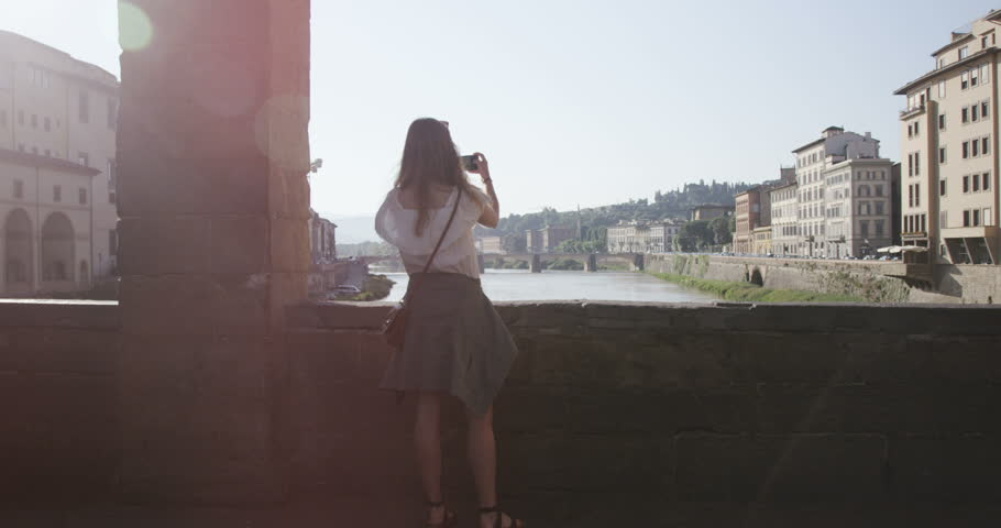 Girl taking photos on bridge in Florence, Italy #1012775024