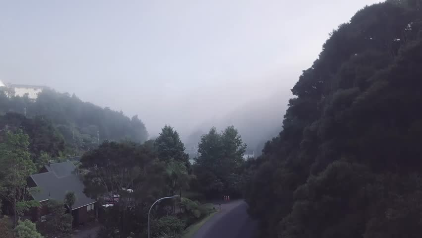 Aerial, flying up through morning mist. New Zealand, land of the long white cloud, beautiful seaside town Paihia is often covered in clouds in the early morning in the bay of islands. | Shutterstock HD Video #1012829144