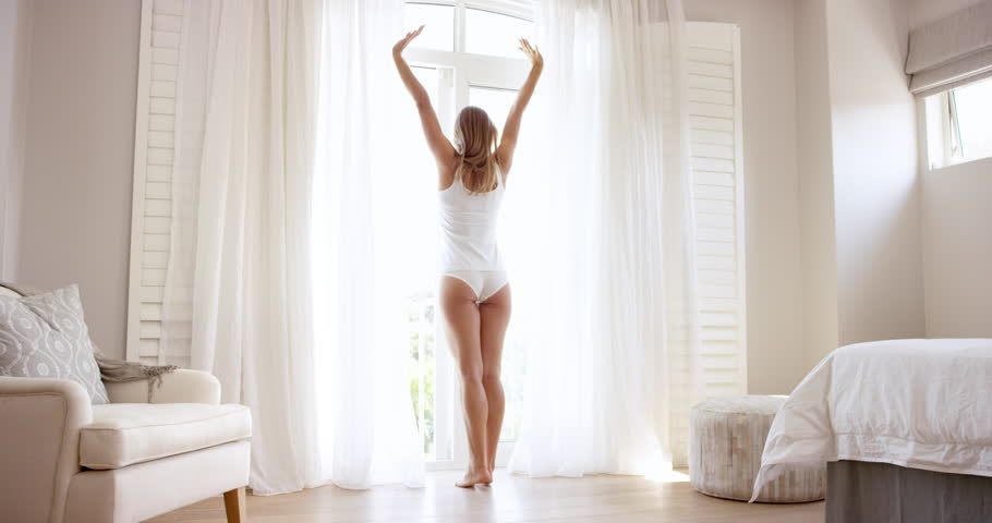 Attractive young woman opening curtains in luxury hotel room stretching at window wearing white underwear RED DRAGON