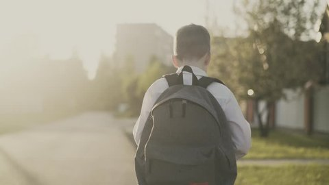 CU, Tracking, Back view: Portrait of a schoolboy, with a knapsack behind his back, in school uniform. He goes on the road from school and counts on his fingers, he thinks.