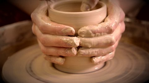 Creating vase of white clay close-up. The sculptor in workshop makes jug out of clay closeup. Twisted potter's wheel. Master crock. Potter's work close-up. Man hands making clay jug. Handmade. Craft.