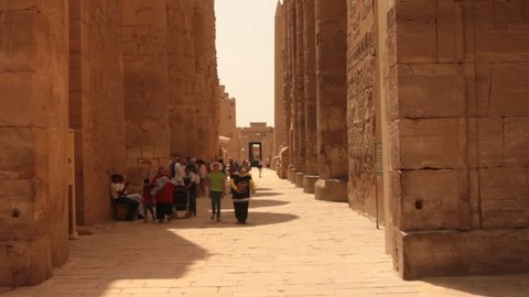 Tourists walk in road in Karnak temple ruins