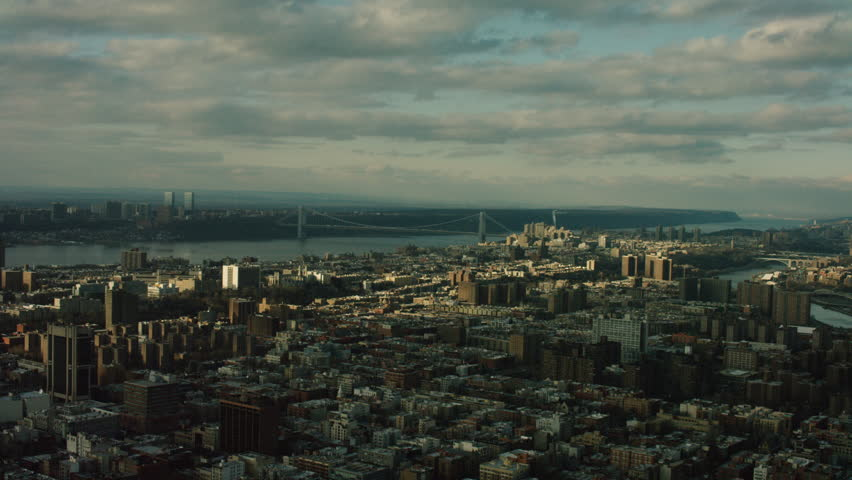 Aerial view of urban city during a cloudy day. Shot of New York City and George Washington Bridge in the distance. Shot with a RED camera. 4k footage.
