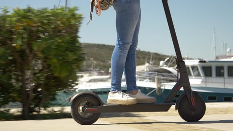Mid shot - Female riding electric scooter. Modern transportation gadget and popular futuristic device among young people