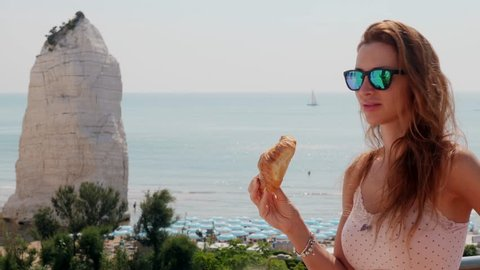 Woman eating croissant in front of sea. Beach of Pizzomunno famous white rock, Puglia, Italy.