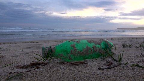 Empty single use plastic bottle discarded on sandy beach