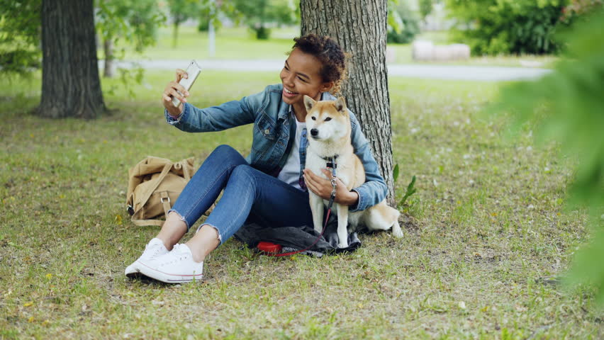 Pretty young girl blogger is taking selfie with purebred dog outdoors in city park cuddling and fondling beautiful animal. Modern technology, loving animals and nature concept.