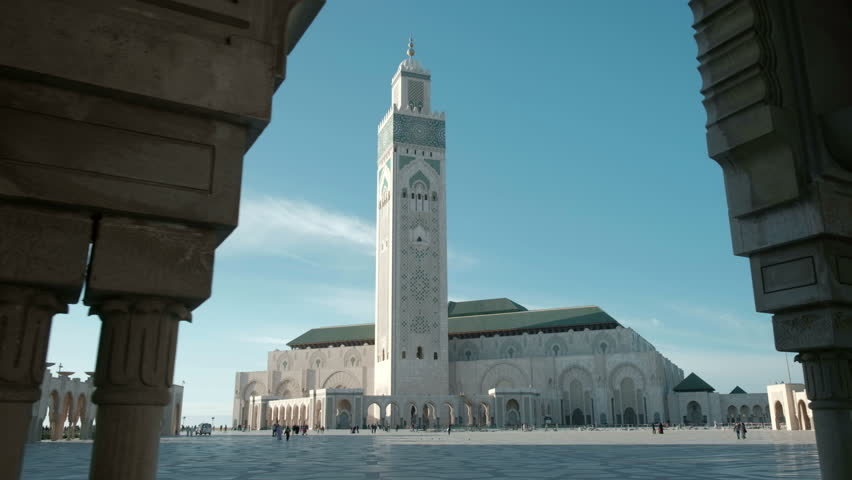 Camera tracking right framed view through arches to reveal Hassan II Mosque and square in late afternoon in Casablanca, Morocco