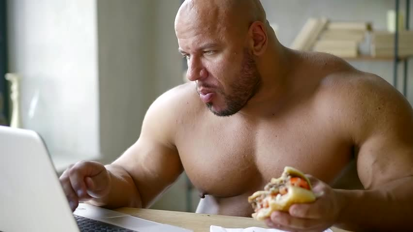 male athlete with big muscles sitting at the table working on laptop and eating triple Burger with beef Patty