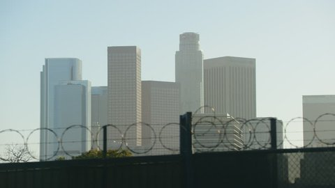 Skyscrapers of Los Angeles seen behind a barb wire sliding gate (daytime)