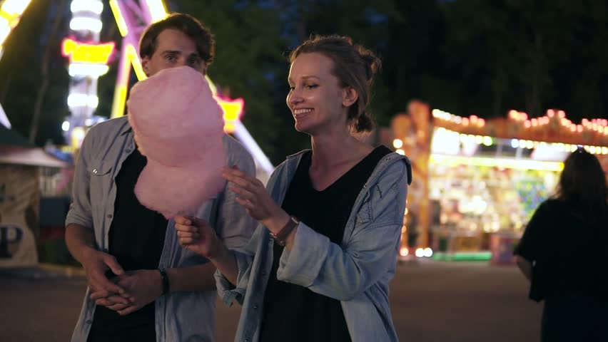 Young hipster couple are having time together in the amusement park at night. Feeding each other with pink cotton candy. Front view | Shutterstock HD Video #1012918514