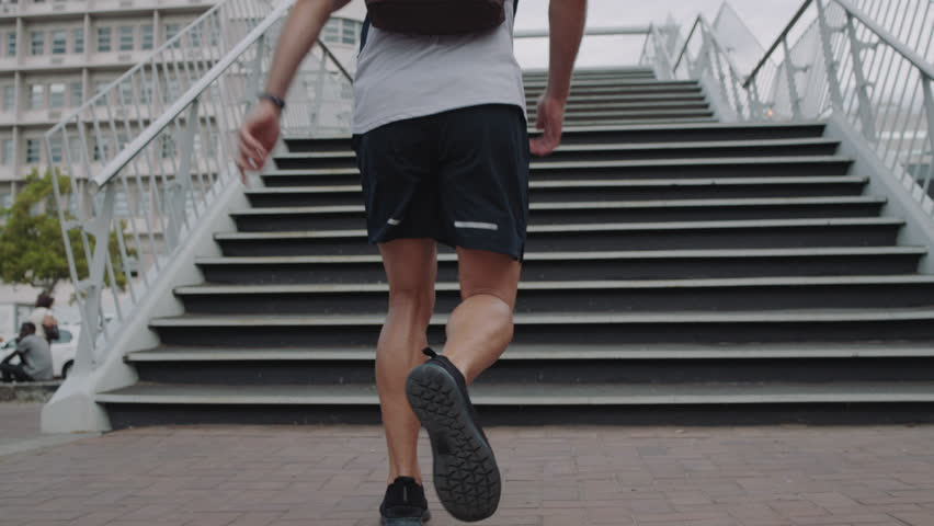 Young man athlete legs running up stairs training intense cardio workout exercise male runner feet jogging on steps in urban city background slow motion | Shutterstock HD Video #1012929014