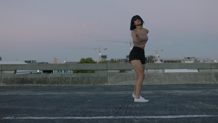 dancing woman attractive hispanic street dancer in city performing contemporary hip hop moves enjoying modern dance expression at sunset #1012939304
