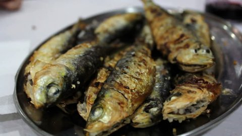 Taking grilled sardines from a silver plate