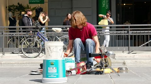 Bologna, Italy, 20 April 2018 - street drummer play with pots and people offer money tips for the artistic performance