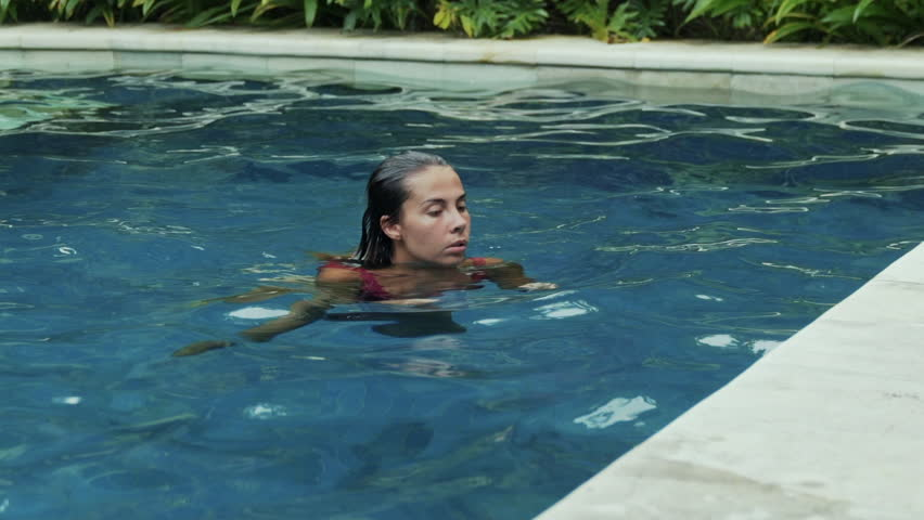 A beautiful brunette with short wet hair in a raspberry swimsuit jumps out of the blue pool, gets into her arms, has a big chest, a thin waist and a round ass, a slow-motion shot.