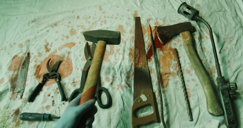 POV hands taking chisel and hammer from torture tools placed on bloody cloth