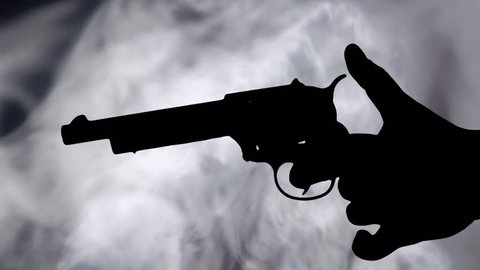 A female hand holding a revolver gun appearing and shooting. Silhouette shot over dense grey smoke.