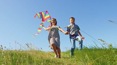 Happy childhood - Boy and girl run down the green hill with a flying kite at clear blue sky background. Wide shot, slow motion