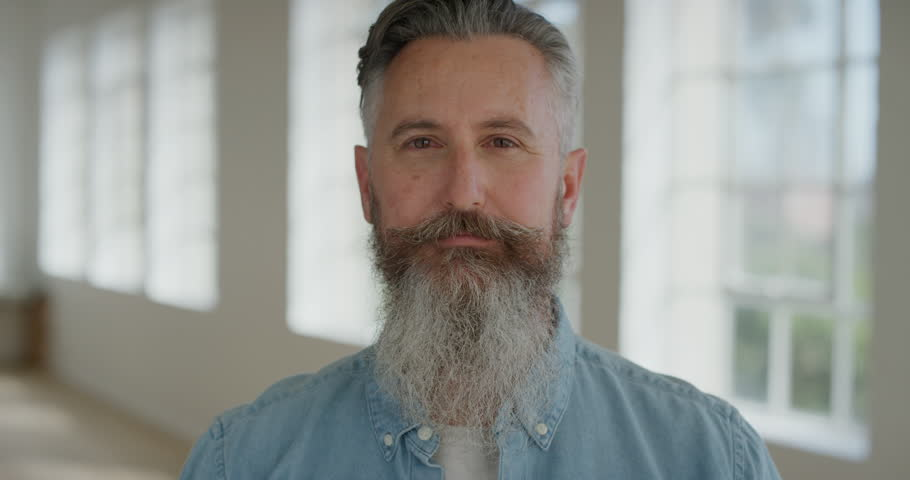 portrait of mature caucasian man smiling cheerful looking at camera enjoying successful lifestyle happy senior male with stylish beard real people series