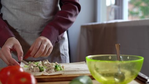 The process of preparing doner, a young woman dressed in an apron in her kitchen wraps pita bread with sliced cucumbers, cabbage and chicken.