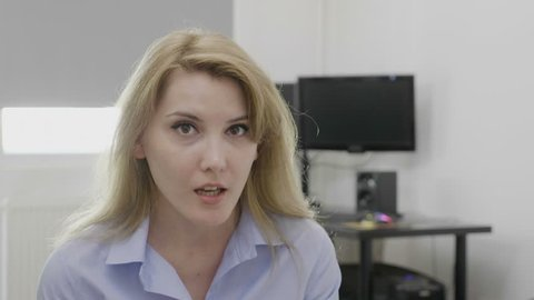 Young blonde office woman at work saying omg oh my God reaction with astonished face and opened mouth