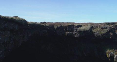 Flying below ground, landing in Arnarker cave Iceland, drone aerial.