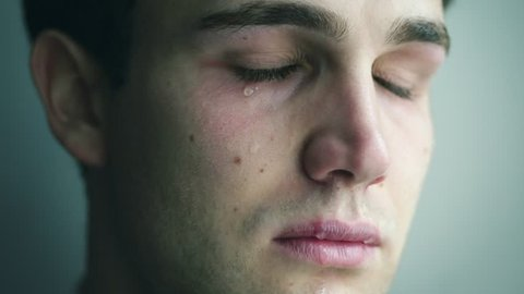 close up portrait of depressed young beautiful man cries.Depression, malaise, sadness