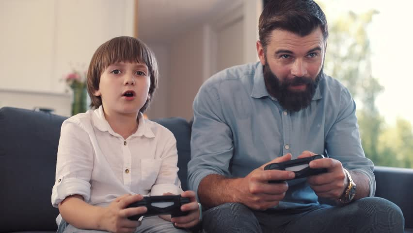 Happy focused dad and son looking at screen, holding joysticks in hands. Little boy playing videogame wih dad. Men winning, high-fiving. Home. Coziness. Indoors. | Shutterstock HD Video #1013039114