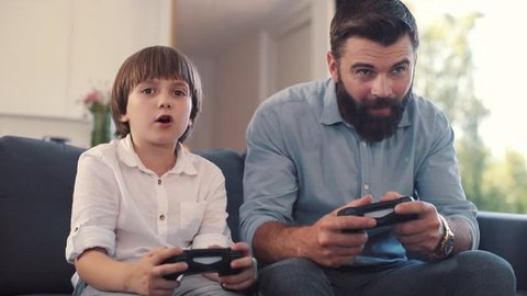 Happy focused dad and son looking at screen, holding joysticks in hands. Little boy playing videogame wih dad. Men winning, high-fiving. Home. Coziness. Indoors.