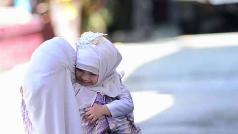 Concept is Happy Indonesian Muslim family,Daughter rushes into her lovely mother's arms and gives her a big hug.