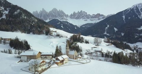 Aerial drone view of famous Santa Maddalena mountain village in the Dolomites with snowy Gruppo delle Odle mountain range in the background in winter, Val di Funes, South Tyrol, Italy, Europe
