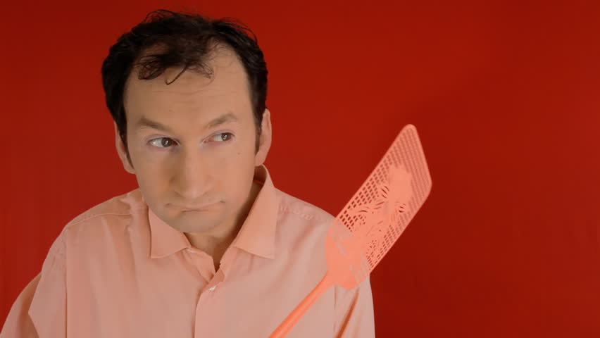 A funny ugly man trying to squash a fly with a swatter, but ending up hitting himself on the head. Red background.  | Shutterstock HD Video #1013054684