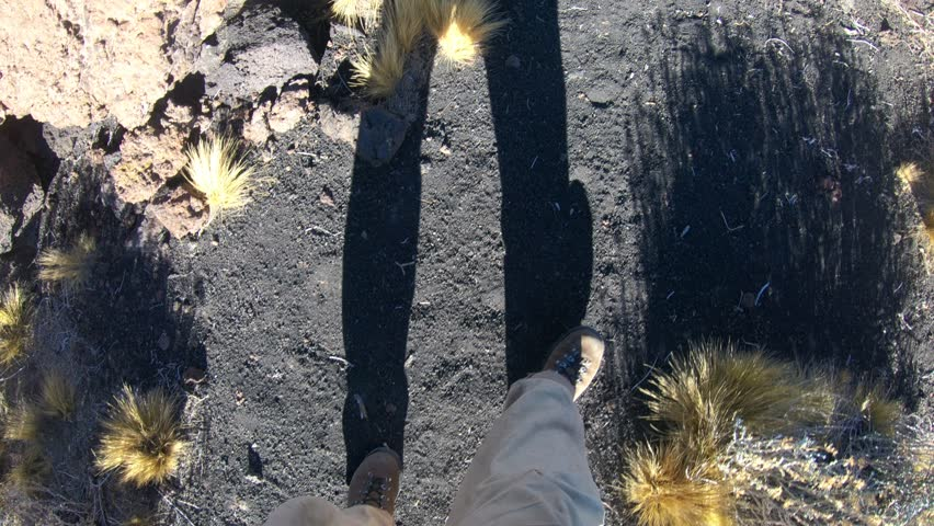 Stabilized camera ponting down to the feet os a man, walking over black small lapillis rocks and then pointing up to Payun Liso volcano on background, at La Payunia, Malargüe, Mendoza.