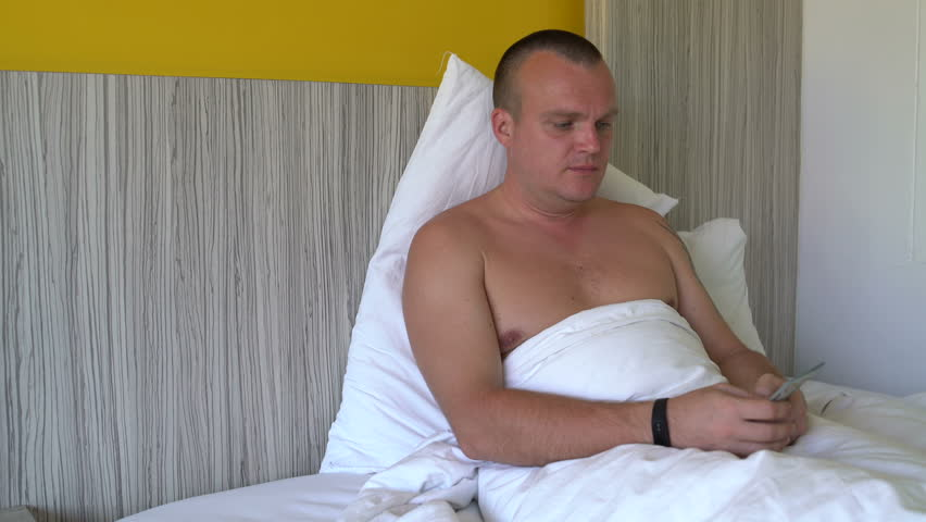 A man is lying in bed and counting money   Shutterstock HD Video #1013075714