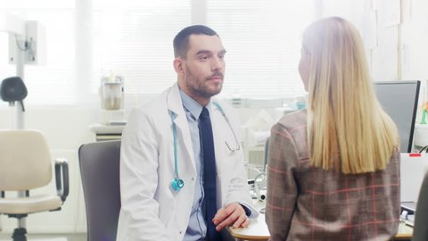 In Medical Office Concerned Doctor Talks with a Beautiful Blonde Woman. Health Care Professional Consultation in the Bright Modern Office. Shot on RED EPIC-W 8K Helium Cinema Camera.