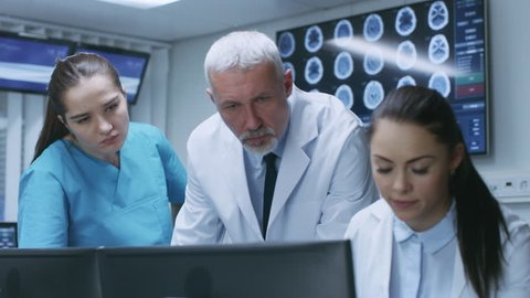 Diverse Team of Medical Scientists Solve Problems and Point at Computer Screens Showing CT, MRI Scans. Neurologists / Neuroscientists Working in Brain Research Laboratory. Shot on RED EPIC-W 8K.