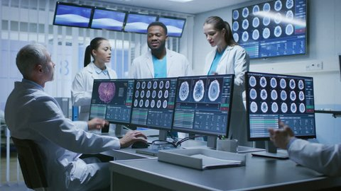 Team of Professional Medical Scientists Work in the Brain Research Laboratory. Neurologists / Neuroscientists Having Heated Discussion Surrounded by Monitors With CT, MRI Scans. Shot on RED EPIC-W 8K.