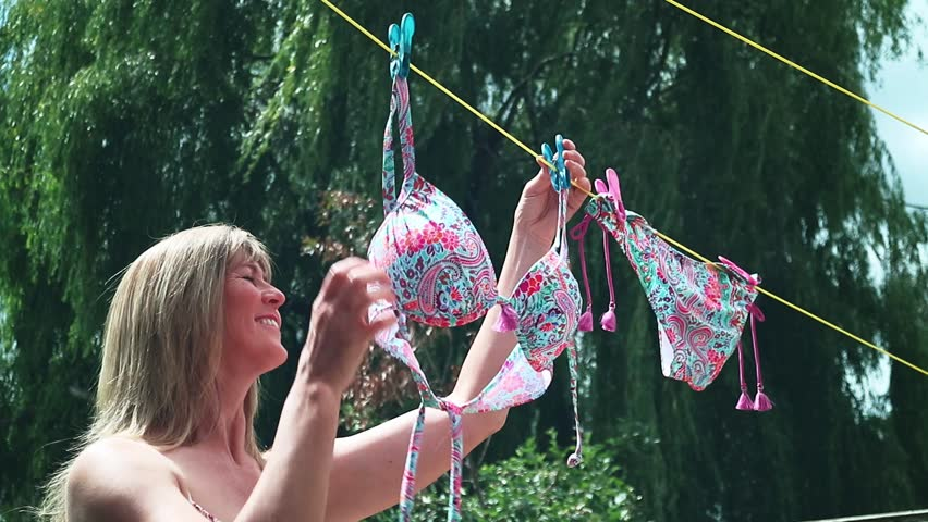 Woman hanging out a bikini to dry on a washing line
