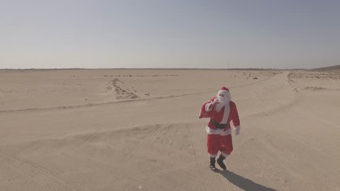 Aerial view, drone, air shoot. Santa Claus with sack walks on sand, found asphalt road in desert. Dlog profile. Comes, coming to town for Christmas at summer in Africa, UAE