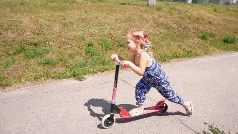 Little girl quickly rides Kick scooter along path in summer country side park. Slow Motion